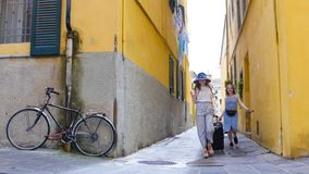 Two young smiling women walking through the narrow yellow streets with luggage royalty free stock photography