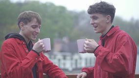 Two young smilling guys in red jackets cheers with coffe cups and smile outdoors Friends spend time outdoors together. Two men in red jackets cheers with coffee stock video footage
