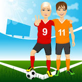 Two young soccer players friends. And rivals of competing teams together on a soccer field Royalty Free Stock Image