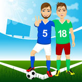 Two young soccer players friends. And rivals of competing teams together on a soccer field Royalty Free Stock Photos