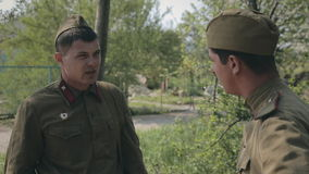 Two young soldier in uniform standing in the. Forest and smoking stock video