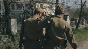 Two young soldiers coming with guns in uniforms on. The road and communicating stock footage