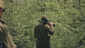 Two young soldiers with the rifles walk in the. Two young soldiers with the rifles go through the woods stock video