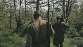 Two young soldiers with rifles walk in the woods stock video footage