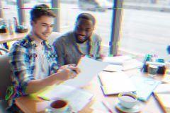 Two young specialists smiling while working with documents. Working together. Cheerful enthusiastic young designers sitting in a cafe and smiling while stock photo