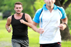 Two young sport man jogging together at roadside Stock Images