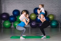 Two young sports mom and baby girls do exercises together in the royalty free stock photo