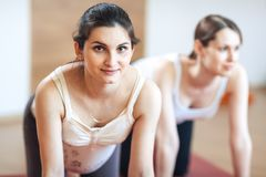 Two young sports pregnant woman doing stretching exercise, looking at camera smiling stock image