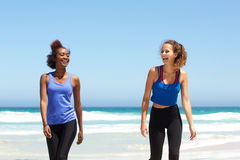 Two young sports women laughing at the beach after workout Royalty Free Stock Photos