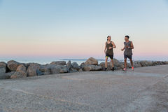 Two young sportsmen running together. At the beach Stock Photography