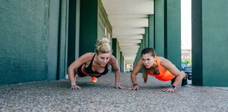 Sportswomen doing push-ups. Two young sportswomen doing push-ups together outdoors royalty free stock photos