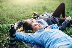 Two young sportswomen laying on grass with eyes closed relaxing after outdoor workout Royalty Free Stock Image