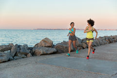 Two young sportswomen running together and talking Royalty Free Stock Image
