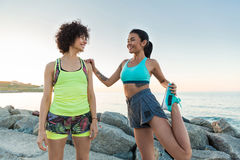Two young sportswomen stretching at the beach Royalty Free Stock Image