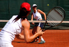 Two young sporty female tennis players having a game in the sun. Two young, fit and tanned sporty female tennis players having a game in the sun on red asphalt royalty free stock images