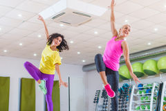 Two young sporty women exercising in fitness studio, dancing, doing cardio, working on balance and coordination. Two young sporty women exercising in fitness Stock Photo