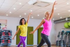Two young sporty women exercising in fitness studio, dancing, doing cardio, working on balance and coordination. Two young sporty women exercising in fitness Royalty Free Stock Photos