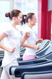 Two young sporty women run on machine Stock Photo