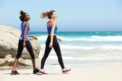 Two young sporty women walking on beach Royalty Free Stock Photo