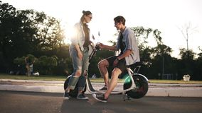 Two young stlylish friends are hanging out together. The boy is sitting on bike and talking to a beaitiful blonde girl. In front. Happy, carefree, smiling stock footage