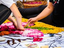 Two young street artists, working on the ground, a colorful design made of flowers. Petals and spices, seen from below royalty free stock images