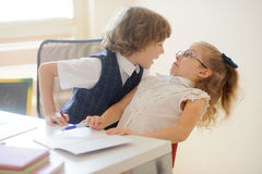 Two young student, boy and girl sitting at a school desk. Royalty Free Stock Images