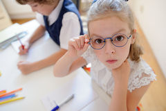 Two young student of an elementary school sitting at a desk. Royalty Free Stock Image