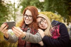 Two young student girlfriend with long hair and glasses walking Royalty Free Stock Image