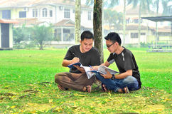 Two young student reading books. In front of class Royalty Free Stock Images