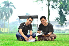 Two young student reading books. In front of class Stock Photo
