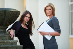 Two young fashion business women with notebook Royalty Free Stock Photo