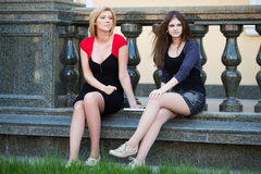 Two young fashion beautiful women sitting on balustrade. Two young happy fashion beautiful women sitting on balustrade Royalty Free Stock Photos