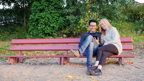 Two young students chatting on a park bench. Enjoy tablet. Korean man and Caucasian woman. Young man and woman talking in the park, enjoy the tablet. Caucasian stock video footage