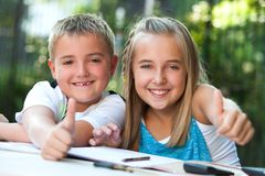 Kids doing thumbs up at desk. Royalty Free Stock Photos