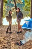 Two young students are going for a walk from forestal campsite. They are standing near tent and bonfire. There are river nearby stock image