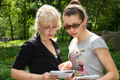 Two young students reading. In the park Stock Images