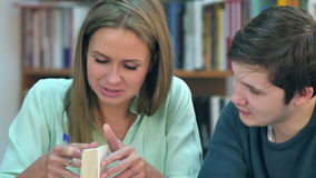 Two young students reading a book in library stock video footage