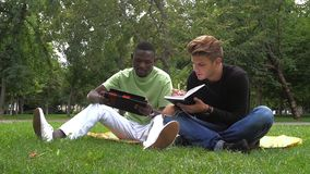 Two young students reading books at the school stock footage