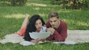 Two young students reading the synopses and prepares to exams in summer park stock video
