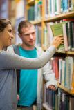 Two young students selecting a book in the library Royalty Free Stock Images