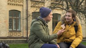 Two young students sits at the bench in park near university. Two students walks in park near the university. Friends are discussing some educational material stock video