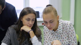 Two young students sitting at the table in the audience and discussing the task. Businessladies making a decision in front of the monitor stock footage