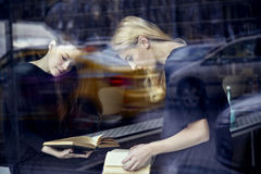 Two young students women in a library reading books. Sitting near window. Education concept stock photo