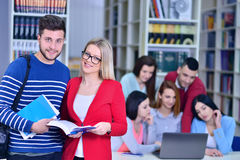 Two young students working together at the library Stock Photos