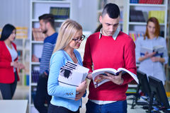 Two young students working together at the library Royalty Free Stock Image