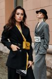 Two young stylish beautiful women fashion models are posing in street, wearing pantsuit, hat, having purse on waist. stock photography