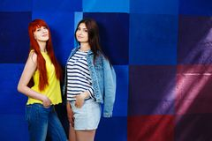 Two young stylish girls standing close on bright background stock images