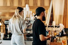 Two young stylish people,a thin blonde girl and a man with beard,wearing casual clotes,cook coffee in a modern coffee royalty free stock images