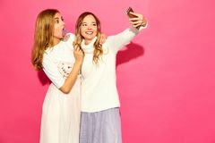 Two young stylish woman models in summer hipster clothes stock images