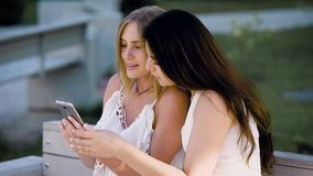 Two young stylish women sitting on bench and watching smartphone in summertime. Girls in white summer clothing sharing phone while posing on bench stock video footage